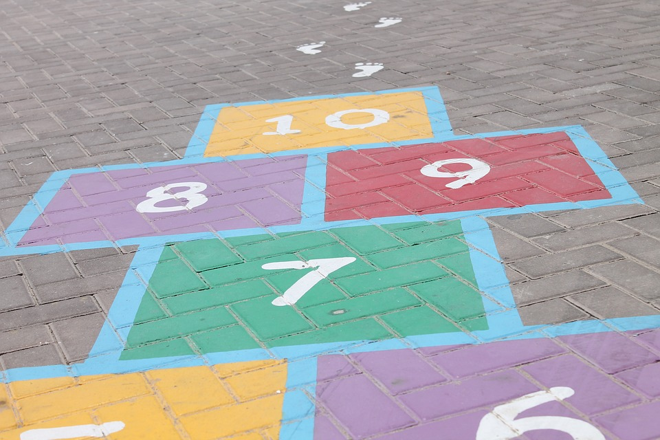 Singing songs while playing hopscotch