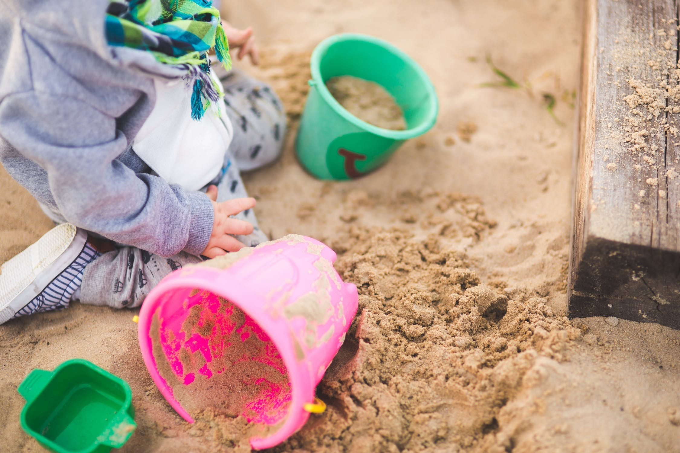 Toddler playing in a sandpit